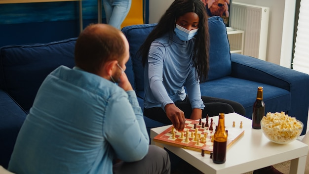 Multiethnic friends playing chess in home living room talking keeping social distancing to prevent illness with covid19 during global pandemic wearing face mask. diverse people enjoying board games
