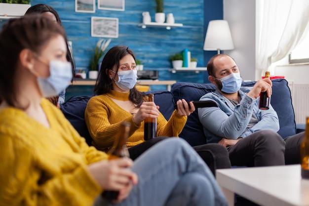 Многонациональные друзья вместе отдыхают и смотрят телевизор с помощью пульта дистанционного управления, сохраняя социальное дистанцирование в маске для лица во время вспышки коронавируса, чтобы предотвратить болезнь.
