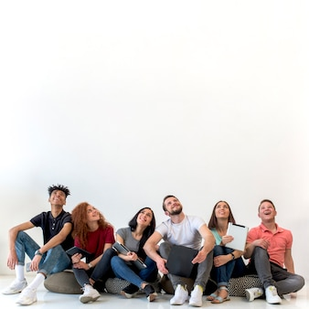 Multiethnic friends sitting on floor looking up against white backdrop