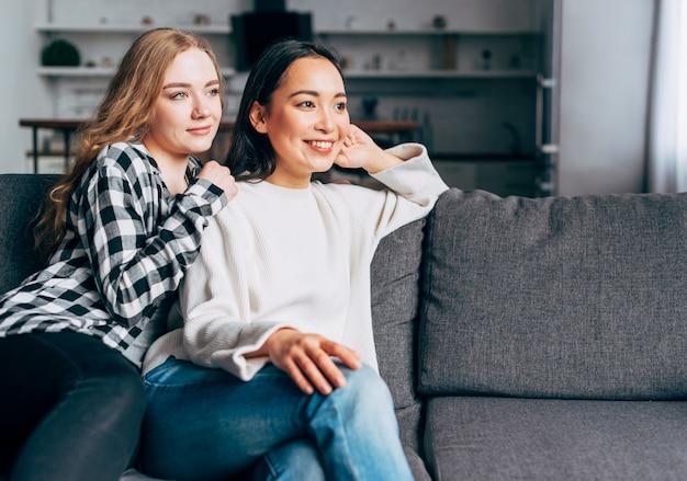 Multiethnic friends sitting on sofa