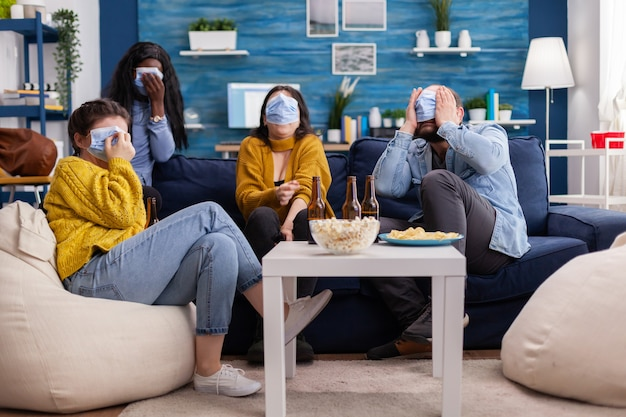 Multiethnic friends socialising looking at terrifying movie on tv sitting on sofa in apartment living room wearing face mask during coronavirus outbreak respecting social distancing.
