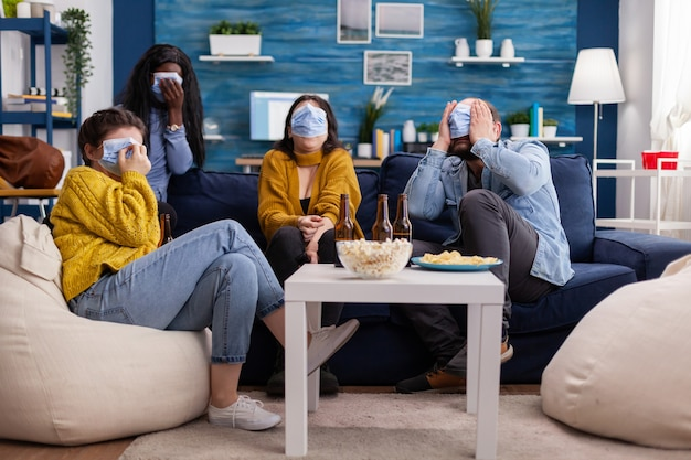 Multiethnic friends socialising looking at terrifying movie on tv sitting on sofa in apartment living room wearing face mask during coronavirus outbreak respecting social distancing. Premium Photo