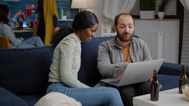 後ろのソファで休んでいるラップトップでオンラインの面白いビデオを見ながら社交する多民族の友人...