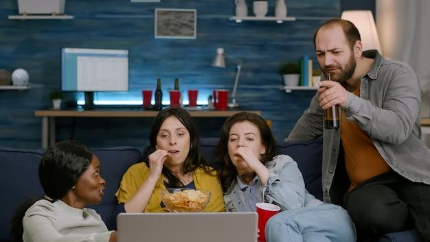 다민족 친구들이 노트북으로 엔터테인먼트 영화를 보면서 함께 시간을 보내고 있습니다.