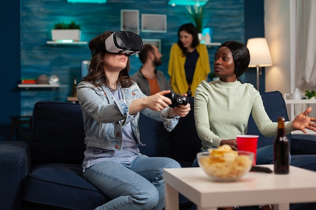 Многонациональные друзья поддерживают женщину во время соревнования по видеоиграм, играя с очками vr с помощью джойстика. группа людей смешанной расы гуляет вместе, развлекаясь поздно ночью в гостиной.