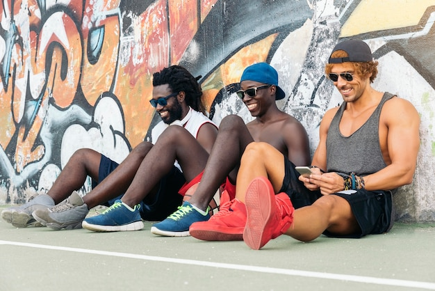 ストリートバスケットボールの試合後の休憩中にモバイルを使用する多民族の友人。
