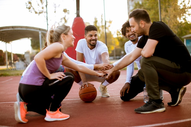 Multiethnic group of basketball players resting on court