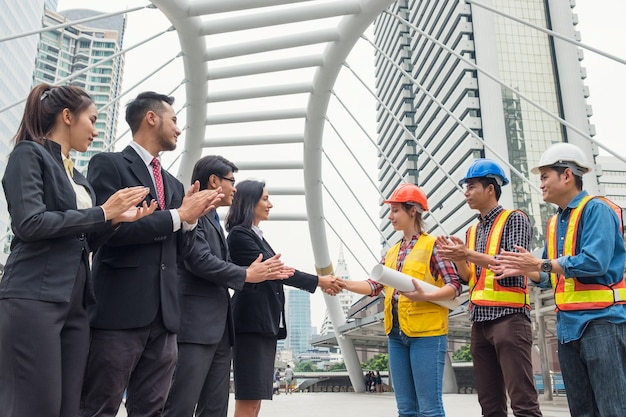 Multiethnic group of business people with engineer partner handshake with contract agreement of business project in urban