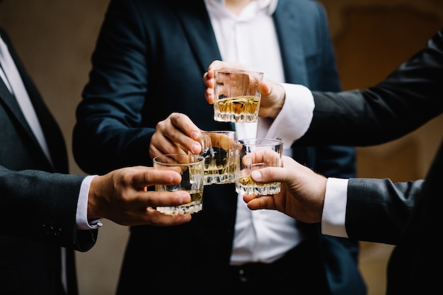 Multiethnic group of businessmen spending time together drinking whiskey and smoking