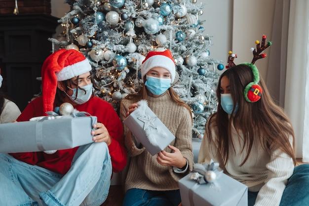 Gruppo multietnico di amici in cappelli di babbo natale sorridenti e in posa per la telecamera con doni nelle mani. il concetto di celebrare il nuovo anno e il natale sotto le restrizioni del coronavirus. vacanza in quarantena