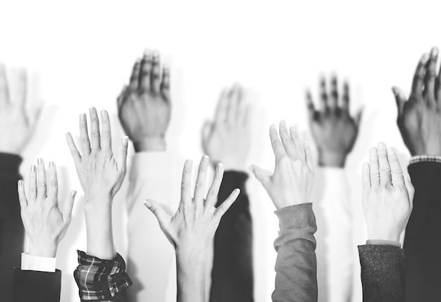 Multiethnic group of hands raised Free Photo
