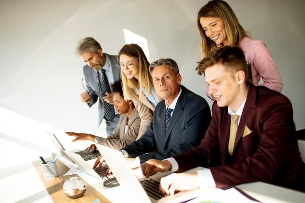 Многонациональная группа деловых людей, работающих вместе и готовящих новый проект на встрече в офисе