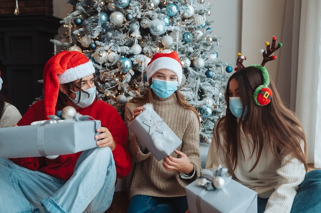 웃 고 손에 선물 카메라에 포즈 산타 모자에있는 친구의 다민족 그룹. 코로나 바이러스 제한에 따라 새해와 크리스마스를 축하하는 개념. 방역 휴가