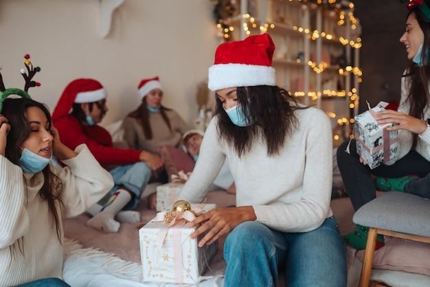웃 고 손에 선물 카메라에 포즈 산타 모자에있는 친구의 다민족 그룹. 코로나 바이러스 제한하에 새해와 크리스마스를 축하하는 개념. 방역 휴가