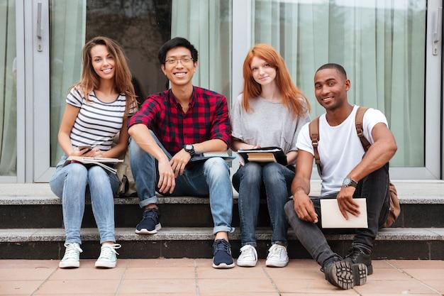 一緒にキャンパスに座っている幸せな若者の多民族グループ