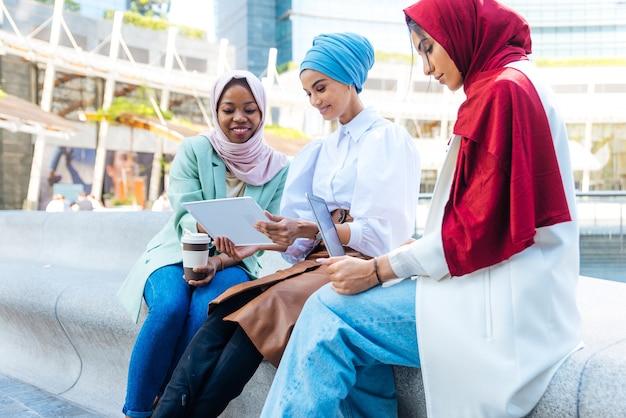 평상복과 전통 히잡을 착용하고 야외에서 즐거운 시간을 보내는 다민족 이슬람 소녀 - 3명의 아랍 소녀 프리미엄 사진