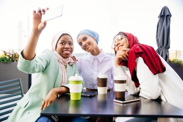 Многонациональная группа мусульманских девушек в повседневной одежде и традиционных хиджабах на открытом воздухе