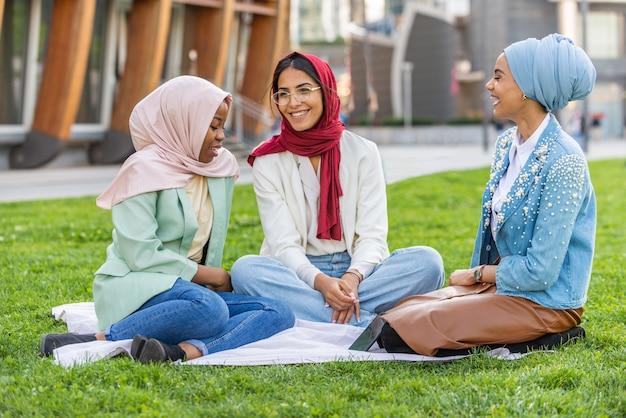 캐주얼 옷을 입고 야외에서 전통적인 히잡 결합을 하는 다민족 이슬람 소녀들