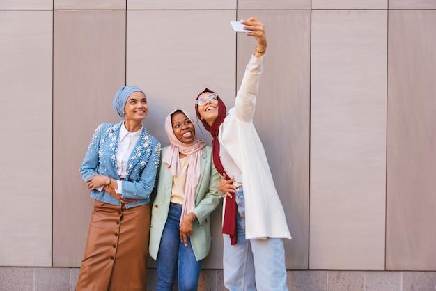 カジュアルな服と伝統的なヒジャーブの絆を身に着けているイスラム教徒の女の子の多民族グループ