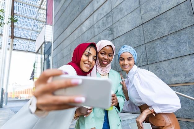 カジュアルな服と伝統的なヒジャーブを身に着けているイスラム教徒の女の子の多民族グループ