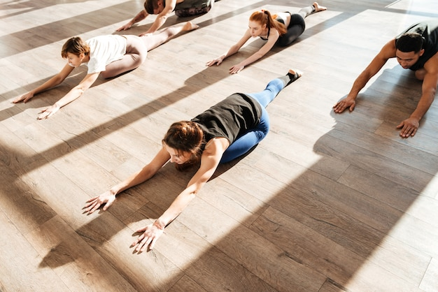 Многонациональная группа людей, делающих упражнения на растяжку в студии йоги
