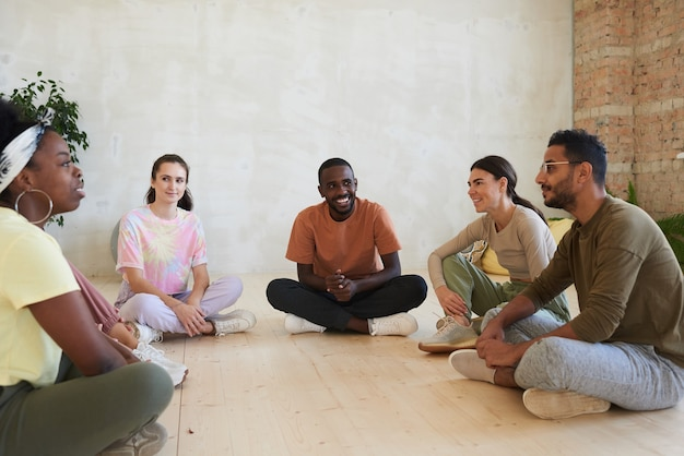 床に座ってお互いに何かを話し合う多民族の人々のグループ