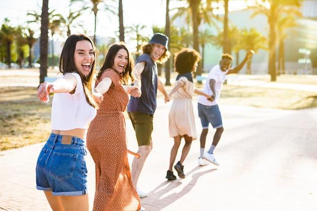 Многонациональная группа молодых друзей счастливо бегает вместе, держась за руки