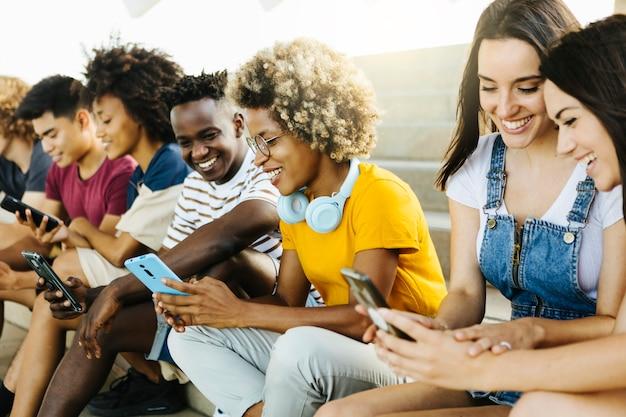도시 계단에 앉아 있는 동안 휴대 전화를 사용하는 젊은 친구들의 다민족 그룹