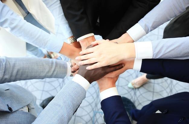 お互いの上に手を置いている若者の多民族のグループ。手を積み重ねる若いビジネスマンの画像をクローズアップ。
