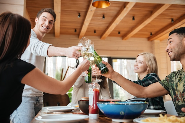 Multiethnic group of people clinking glasses and bottles at the table at home