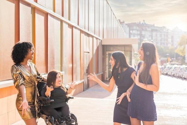 휠체어 장애인 친구가 있는 다민족 그룹은 새해 전야 파티 건강 관리를 축하합니다.