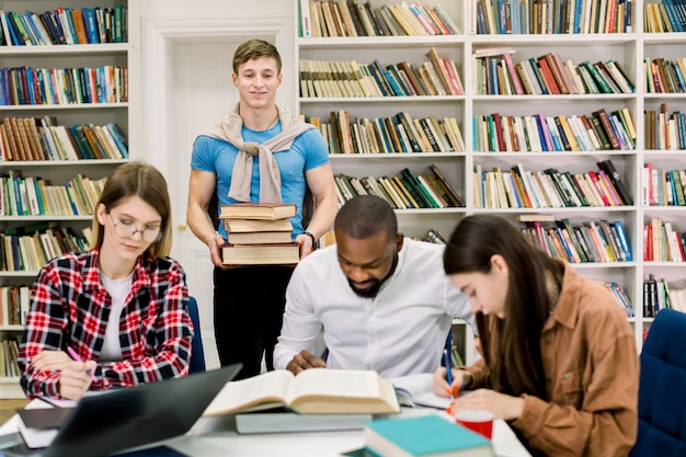 Multiethnic group of young people, students, studying together at the table, reading books. young boy holding stack of many books stands behind the table and looks at his friends