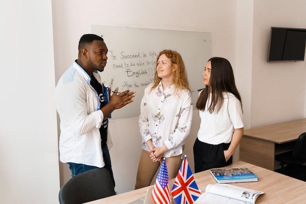 多民族の幸せな生徒と黒人教師が外国語を勉強し、クラスで一緒に笑顔で笑いました