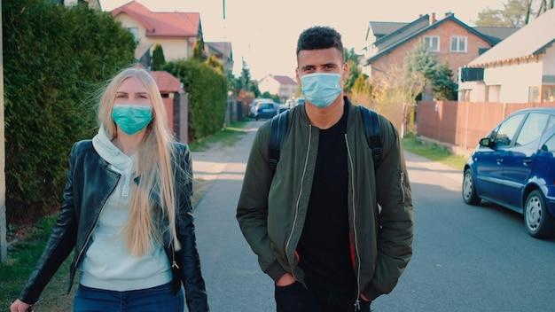 Многонациональные мужчина и женщина в медицинских масках идут по улице в жилом массиве, тратят ...