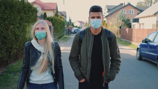 Многонациональный мужчина и женщина в медицинских масках идут по улице в жилом комплексе