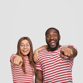 Adolescenti felicissimi multietnici vestiti con abiti a righe, puntano alla telecamera con le dita indice