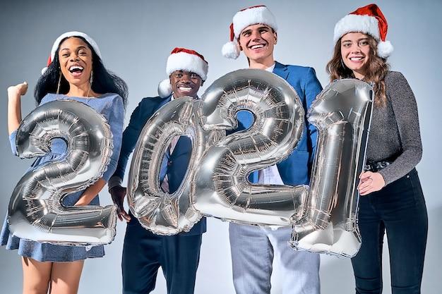 灰色の背景に分離された2021番号の銀の風船を保持している多民族の人々。新年のコンセプト