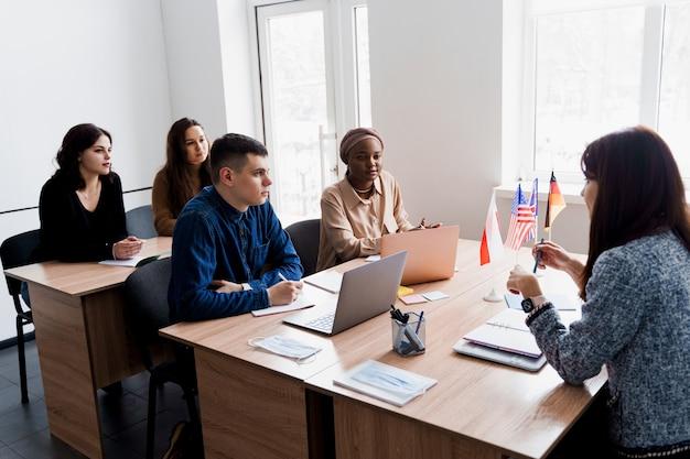 多民族の学生と教師はクラスで一緒に外国語を勉強します。
