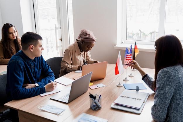 Многонациональные студенты и учитель вместе изучают иностранные языки в классе.