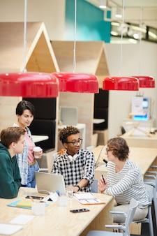 Многонациональные студенты обсуждают проект университета в кафе