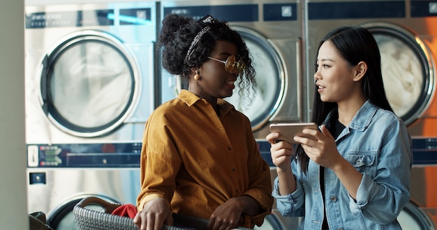スマートフォンで話していると写真やビデオを見て多民族のスタイリッシュな若い女の子。ランドリーサービスで立っている友人。洗濯機が働いている間電話でアフリカ系アメリカ人とアジアの女性。