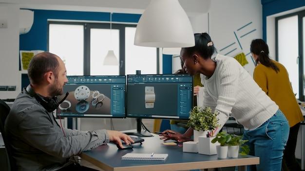 Cadソフトウェアで3d金属部品を設計するためのデュアルモニターセットアップを使用した産業プロジェクトについて話し合う多民族チーム