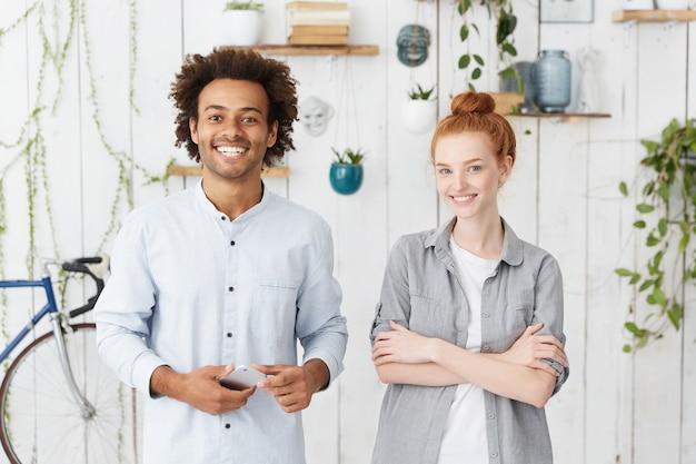 Многонациональная команда из двух сотрудников, стоящих в уютном офисном интерьере