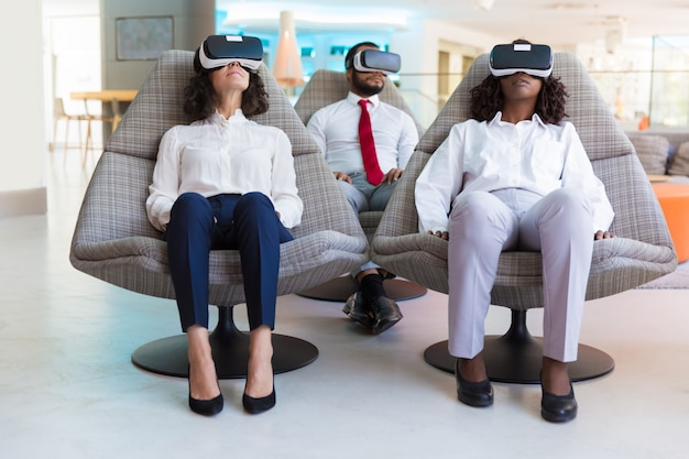 Multiethnic team in vr headsets watching content
