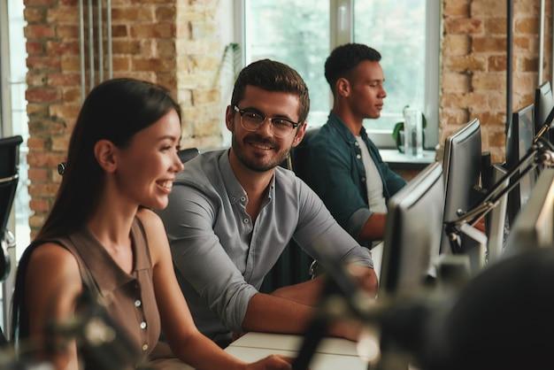 Многонациональная группа совместной работы веселых молодых сотрудников, работающих на компьютерах и разговаривающих с каждым