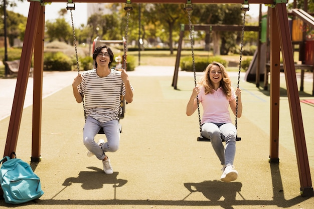 Multiethnic teen friends enjoying swings