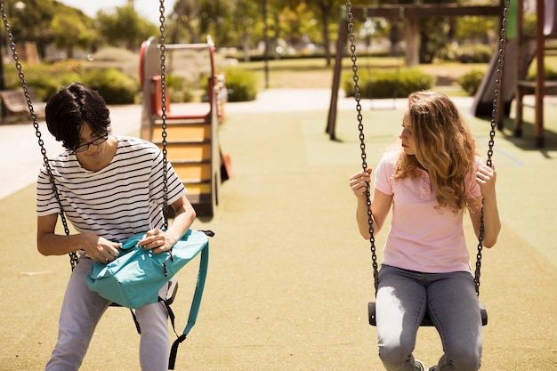 Multiethnic teenagers sitting on swings