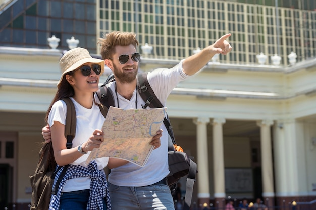 Multiethnic travellers are looking the destination and holding the map