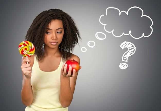 背景にキャンディーとリンゴのどちらかを選択する多民族の女性