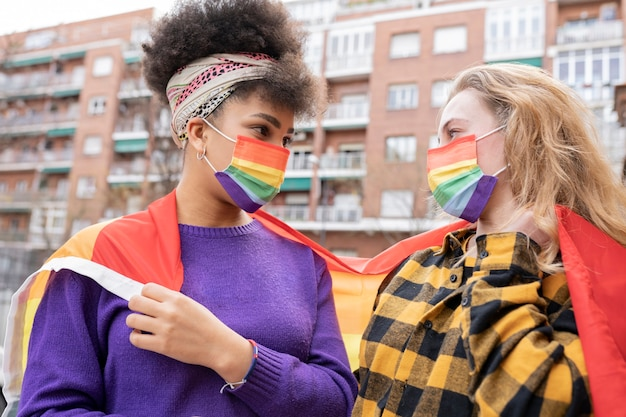 Multiethnic women couple demonstrating for lgbt gay pride